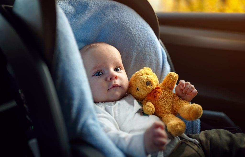 Baby in car seat with teddy bear