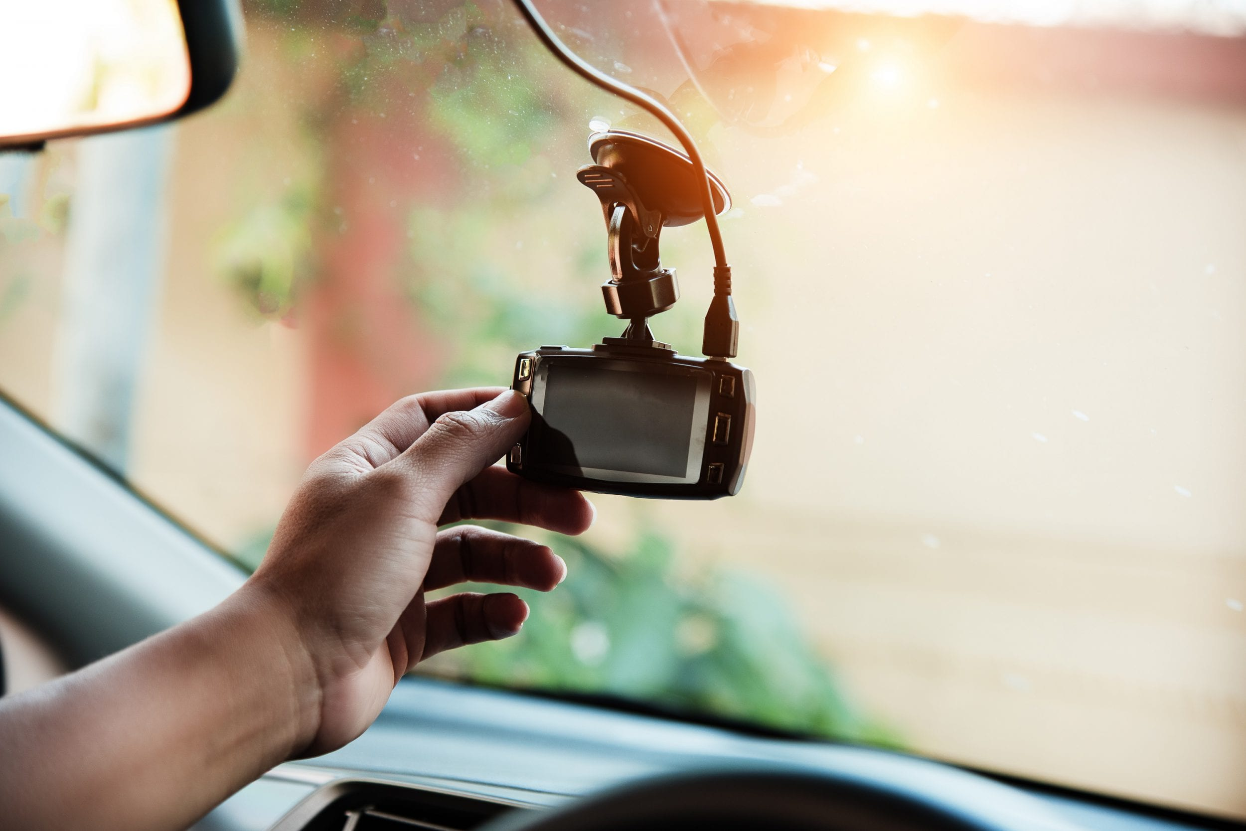 Person setting up dash cam car technology